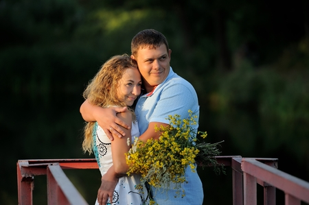 A man hugs a young woman with a yellow bouquet of wildflowers in his hands in the summer at sunset. They look away and smile. Portrait. Close-up. Horizontal orientation of the image. Imagens