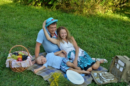Happy family on a picnic in nature. Mom, dad and son have fun and play lying on the grass in the Park in the summer at sunset near the fruit basket. Portrait. Horizontal orientation of the image.