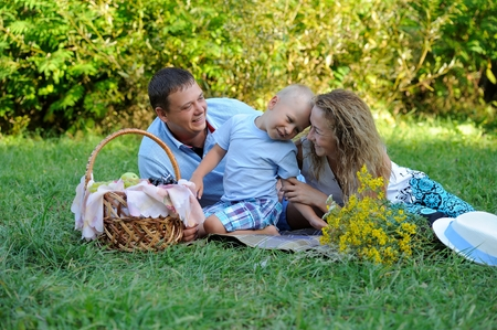 Happy family, dad, mom and little son, play lying on the grass in the Park in the summer at sunset. They look at each other and smile. Portrait. Horizontal orientation of the image. Imagens