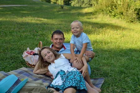Happy mom, dad and baby smile and look at the camera while lying on the blanket in the Park at sunset. Family picnic outdoors. Portrait. Horizontal orientation.