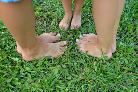 Dad, mom and baby stand barefoot on the green grass. Close-up of adult and childrens feet. The view from the top. Conceptual photo. Landscape orientation.