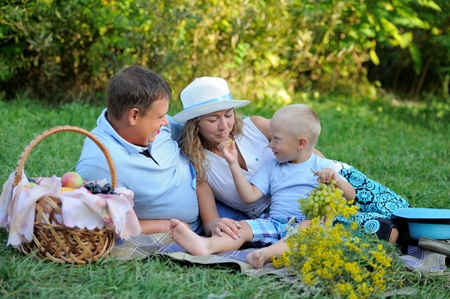 Smiling little boy feeding grapes mom and dad sitting on the grass in the summer at sunset near a basket of fruit and a bouquet of yellow wildflowers. Family picnic outdoors. Portrait. Imagens