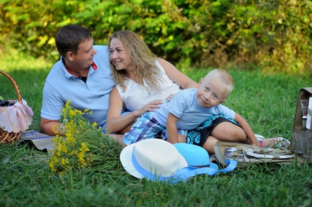 Family picnic in nature. Mom, dad and son relax sitting on the grass in the Park in the summer at sunset. A little boy looks at the camera and smiles. Portrait. Horizontal orientation of the image.