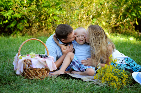 Mom and dad together kiss smiling little son sitting on the grass in the Park in the summer at sunset. Family picnic outdoors. Portrait. Horizontal orientation of the image.