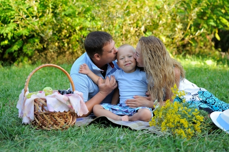 A little boy looks at the camera and smiles, and mom and dad kiss him on both sides, sitting on the grass in the Park in the summer at sunset. Family picnic in nature. Portrait. Imagens