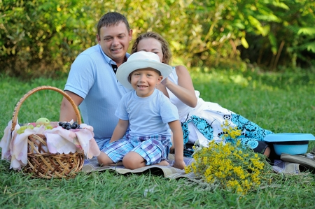 A little boy in a funny white hat smiling sitting on the grass with mom and dad in the Park in the summer at sunset and looking at the camera. Family picnic outdoors. Portrait. Imagens