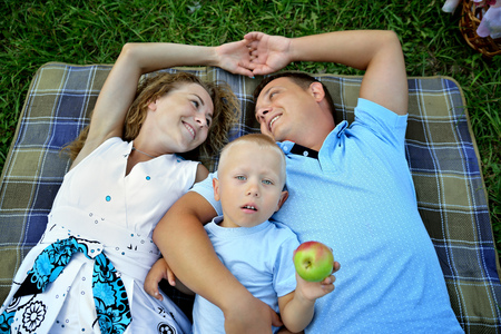 Happy family: mom, dad and baby lie on a blanket on the green grass and hold hands. A child with an Apple in his hand looks up, and the parents look at each other. The view from the top. Concept