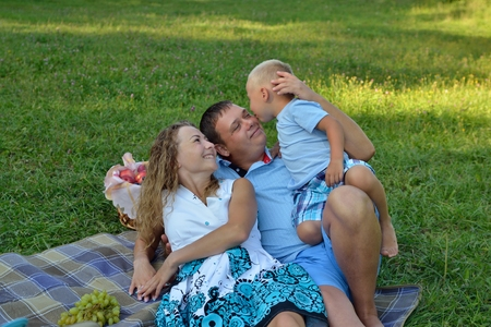 Happy baby kissing his lying dad sitting on his stomach in the Park at sunset. The mother lies nearby, watching them and smiling. Family vacation in nature. Portrait. Horizontal orientation