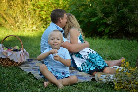 Happy child sitting and smiling on the grass and parents hugging and kissing behind him in the Park at sunset. Family vacation in nature. Portrait. Horizontal orientation