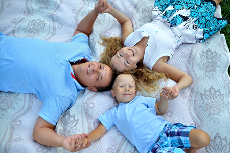 Happy mom, dad and little boy lie on their back head to head and hold hands in the Park at sunset. They look up and smile. The view from the top. Conceptual photo. Landscape orientation Imagens