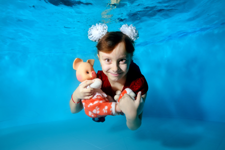 A charming child with a toy pig in her hands swims underwater with her eyes open, smiles and poses for the camera in a red dress on a blue background. Portrait. Horizontal view.