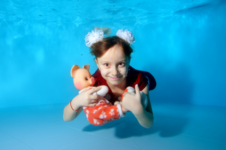 A happy little girl with a toy pig in her hands swims underwater in a dress and bows on her head. She smiles and poses for the camera. Portrait. Horizontal orientation of the image.