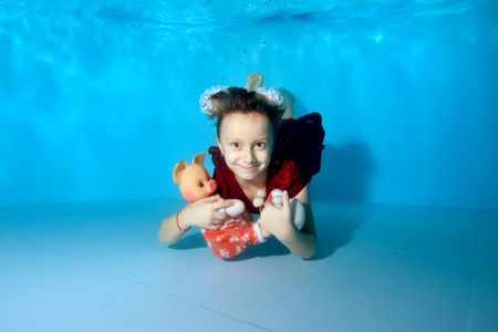 A little girl swims underwater in the pool and holding a toy pig - a symbol of the new year. She smiles and poses for the camera in a red dress and with white bows on her head. Portrait.