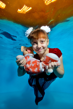 A girl in a red dress swims underwater and holds a toy pig - a symbol of the New year. She poses for the camera with her eyes open and smiles with white bows on her head on a blue background. Portrait