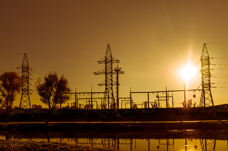 Electric substation and power lines on the background of bright yellow sunset on the riverbank, illuminated by the rear light. Silhouette. Horizontal orientation of the image.