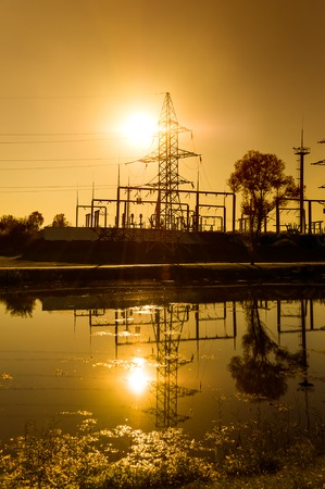 Power lines and substation on the background of bright yellow sunset on the riverbank, illuminated by the rear light. Vertical orientation of the image.