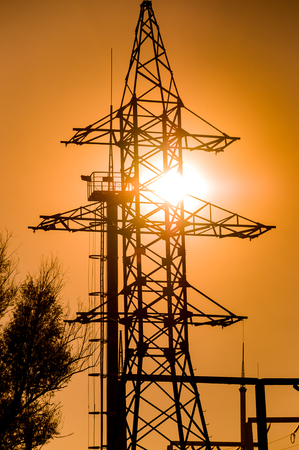 Close-up of the power line tower on a bright yellow sunset illuminated by the rear light. Vertical orientation of the image.
