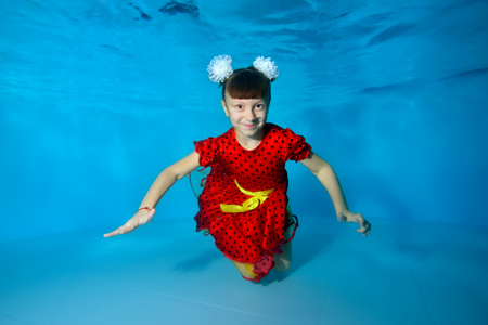 A charming little girl swims under the water with her eyes open, smiles and poses for the camera with her arms outstretched in a red dress on a blue background. Portrait. Horizontal view. Imagens