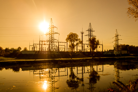 Electrical substation at sunset on the banks of the river. Silhouette. Yellow fill. Horizontal orientation. Imagens