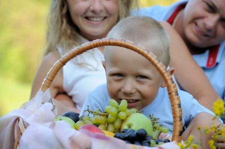 Close-up, little boy having fun and looking through the fruit basket, sitting in nature on a summer day. Family picnic in nature. Portrait. Horizontal view. Imagens