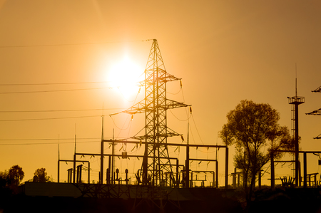Silhouette of an electric substation and power lines on a bright yellow sunset. Horizontal orientation.