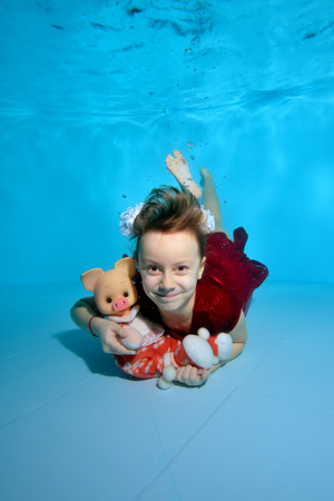 A little girl with a pig in her hands dives to the bottom of the pool with her eyes open. She smiles underwater in a red dress with white bows on her head. Portrait. Vertical view.