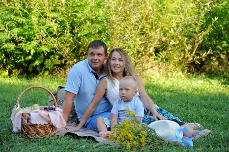 Dad, mom and little boy are sitting on the grass in the Park on a summer day, looking away and smiling. Family picnic in nature. Portrait. Horizontal view.