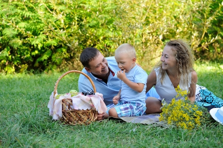 A little boy eats grapes, and mom and dad sit and look at him in the Park on a summer day and smile. Family picnic in nature. Portrait. Horizontal view.