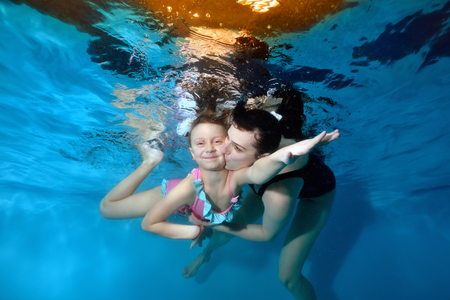 A smiling little girl is swimming underwater with her mother with her eyes open. Mom hugs and kisses her. They play sports. Portrait. Horizontal view. Imagens