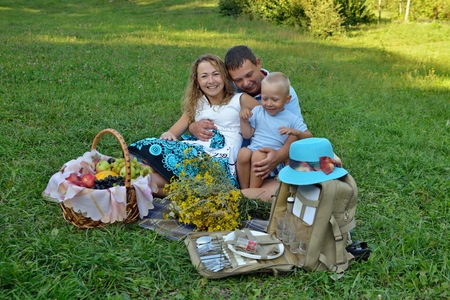 Happy family resting in the Park on the grass at sunset. They play and smile. Family picnic outdoors. Portrait. Horizontal view. Imagens