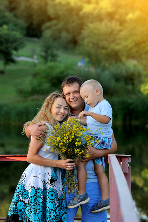 Mom and dad hugging and holding a little boy in the Park by the water at sunset on a summer day. They look at the camera and smile. Family walk in nature. Portrait. Vertical view.