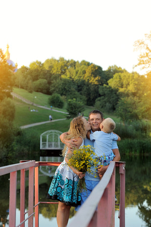 A woman and a child kiss a man standing in the Park by the water at the sunset of a summer day. The family walks in the open air. Portrait. Vertical view. Imagens
