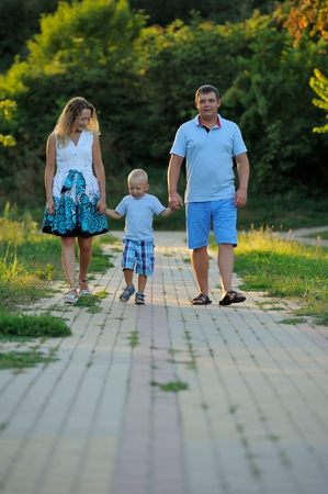 Happy family: dad, mom and little son holding hands and walking along the path in the Park at sunset summer day. The concept of family happiness. Vertical view.
