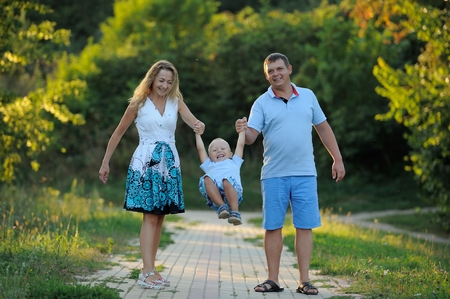 Mom, dad and baby are walking in the Park at sunset on a summer day. Parents shake the child in his arms, as on a swing. Concept. Close up. Horizontal view. Imagens