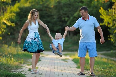 Mom and dad swing the little boy in their arms like a swing, and walk along the path in the Park at the sunset of a summer day. The concept of family happiness. Close up. Horizontal view.