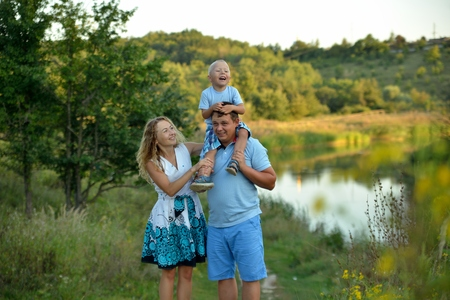 A happy little boy sits on his fathers neck and laughs, and his mother supports him and smiles. Family walks in the Park by the water at sunset summer day. Concept. Portrait. Horizontal view. Imagens