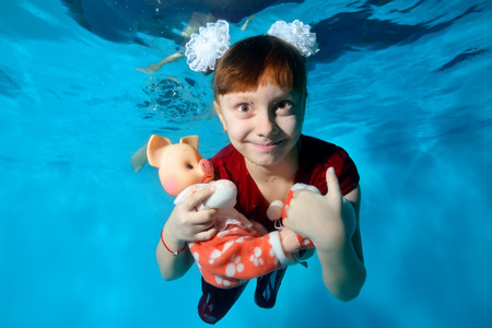 Underwater portrait of a little girl with a pig in her hands, who swims and smiles under the water in the pool with her eyes open in a red dress and with white bows on her head. Imagens