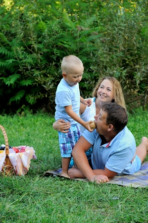 Family picnic in nature. Child feeding an apple dad, who lies in a Park on the grass on a summer day. Portrait. Vertical view. Imagens