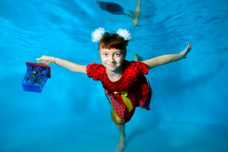 Happy little girl with a gift in her hand swimming underwater in the pool with her eyes open in a red dress and smiling. Portrait. Horizontal view. Imagens
