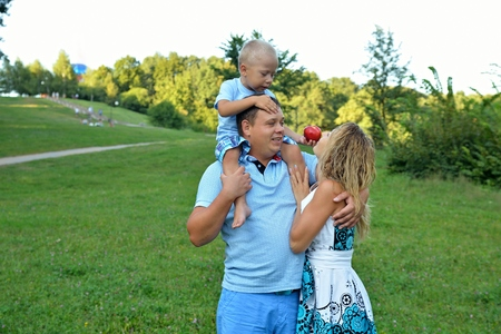 A little boy treats his mother with a red Apple, sitting on his fathers neck in the Park on a Sunny summer day on a green background. Family outdoor activities. The concept of family happiness.