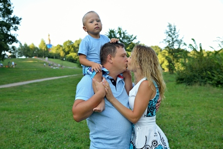A little boy sits on his fathers neck while mom and dad kiss in the Park on a Sunny summer day on a green background. Family walks in nature. The concept of family happiness. Portrait.