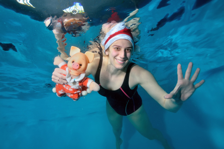 Girl swimming instructor swims underwater and holding a toy pig - a symbol of the New year. She smiles and poses for the camera with her eyes open in Santas hat on her head. Portrait Imagens
