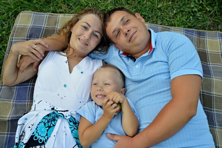 Mom, dad and little son lie and dream on the grass in the Park at sunset summer day. They look up and smile. Portrait. The view from the top. Horizontal orientation of the image.