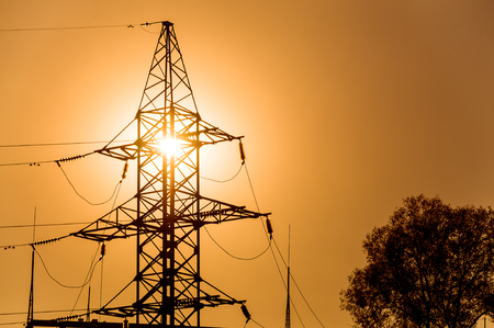 The silhouette of a power line tower at a bright yellow sunset in the back light. Close up. Horizontal orientation of the image.