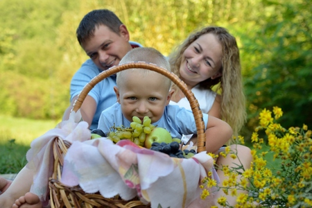A little boy looks through a fruit basket, and mom and dad sit behind him on the grass in the Park, smiling and looking at him on a summer day. Family picnic in nature. Portrait. Horizontal view. Imagens