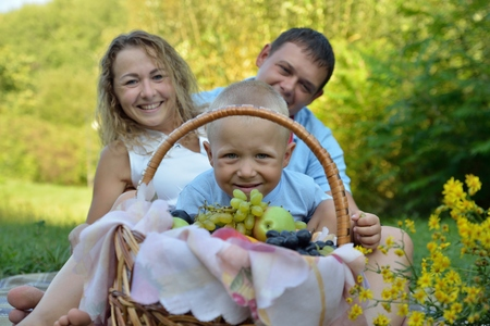 The child smiles and looks through the fruit basket, sitting with mom and dad on the grass in the Park on a Sunny summer day. Family picnic in nature. Portrait. View from ground level.