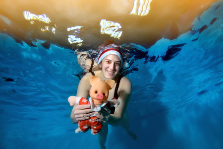 A woman swims under water and holds a toy pig - a symbol of the New year. She poses for the camera with her eyes open and smiles with Santas hat on her head. Portrait.