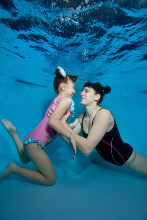 Mom swims and hugs little daughter underwater at the bottom of the pool. They look at each other and smile with their eyes open. Portrait. Vertical view.