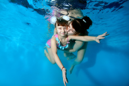 Happy mother kissing and hugging her young daughter under water in the pool. They play sports and smile on a blue background with their eyes open. Portrait. Horizontal view.
