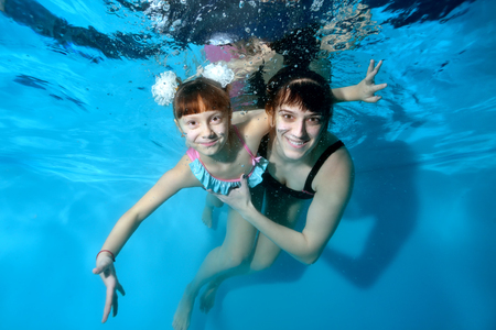 Happy mom and her little daughter play sports and swim underwater in the pool with their eyes open. They hug and smile under the water on a blue background. Portrait. Horizontal view.